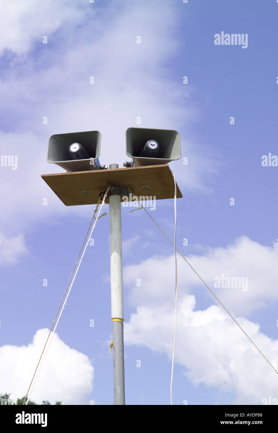 Loudspeakers on a pole with sky in the background at a fete - Stock Image