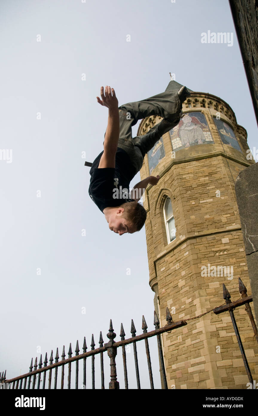 Young man parkour freerunner Aberysytwyth wales UK doing a backflip through the air outside the university - Stock Image