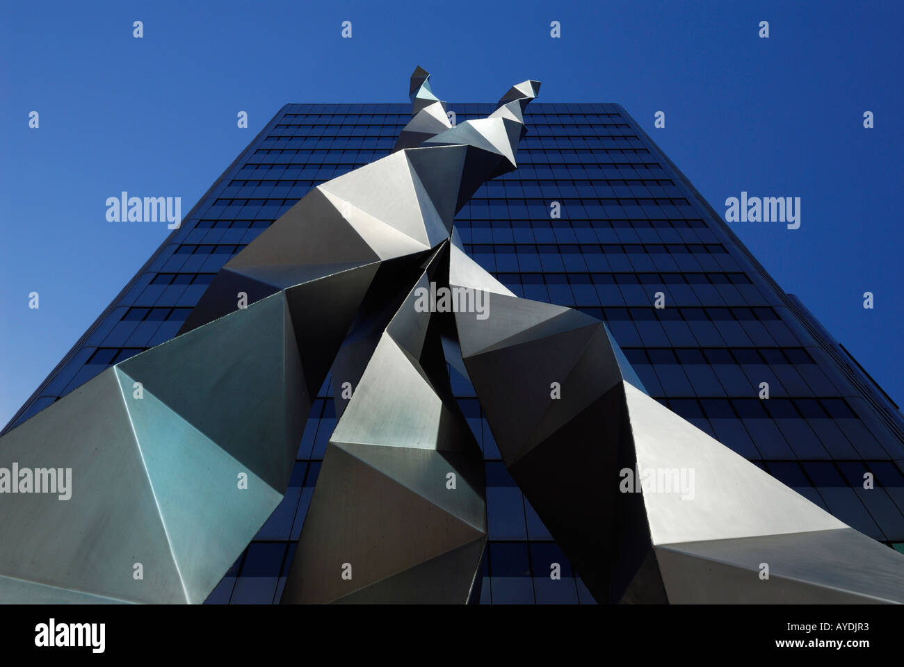 Folded triangular metal steel sculpture against a blue highrise office building and sky in Toronto - Stock Image