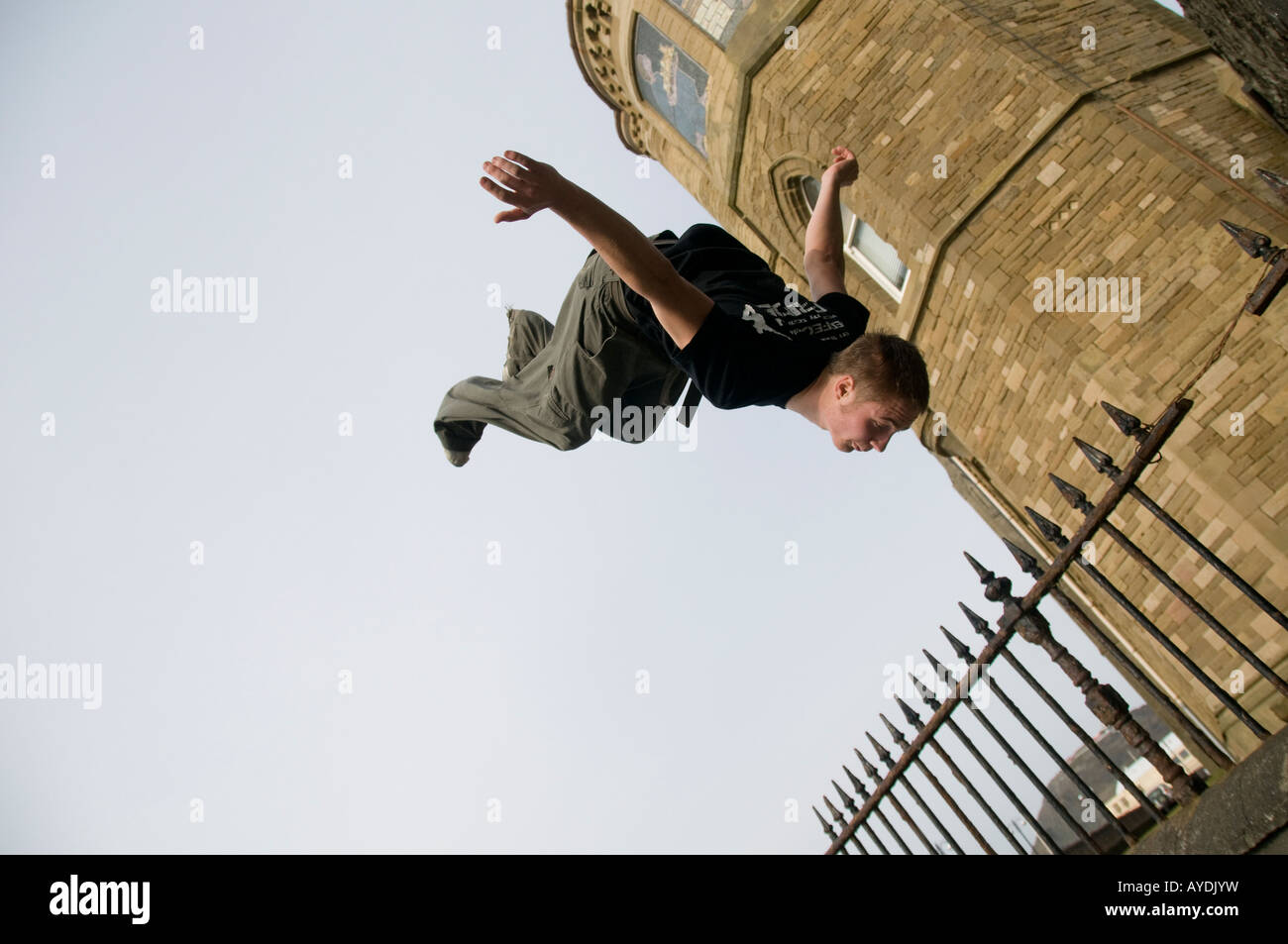 Young man parkour freerunner Aberystwyth wales UK doing a backflip outside the university - Stock Image