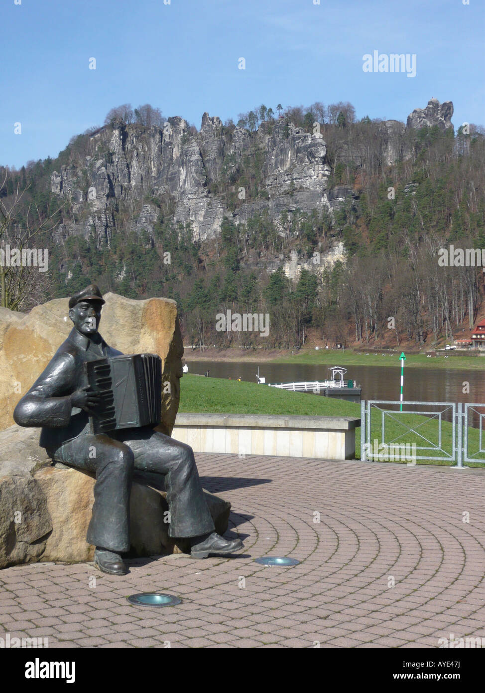 Sculpture of an accordion player in Oberrathen in front of the river Elbe and the rocks of the 'Bastei'. - Stock Image