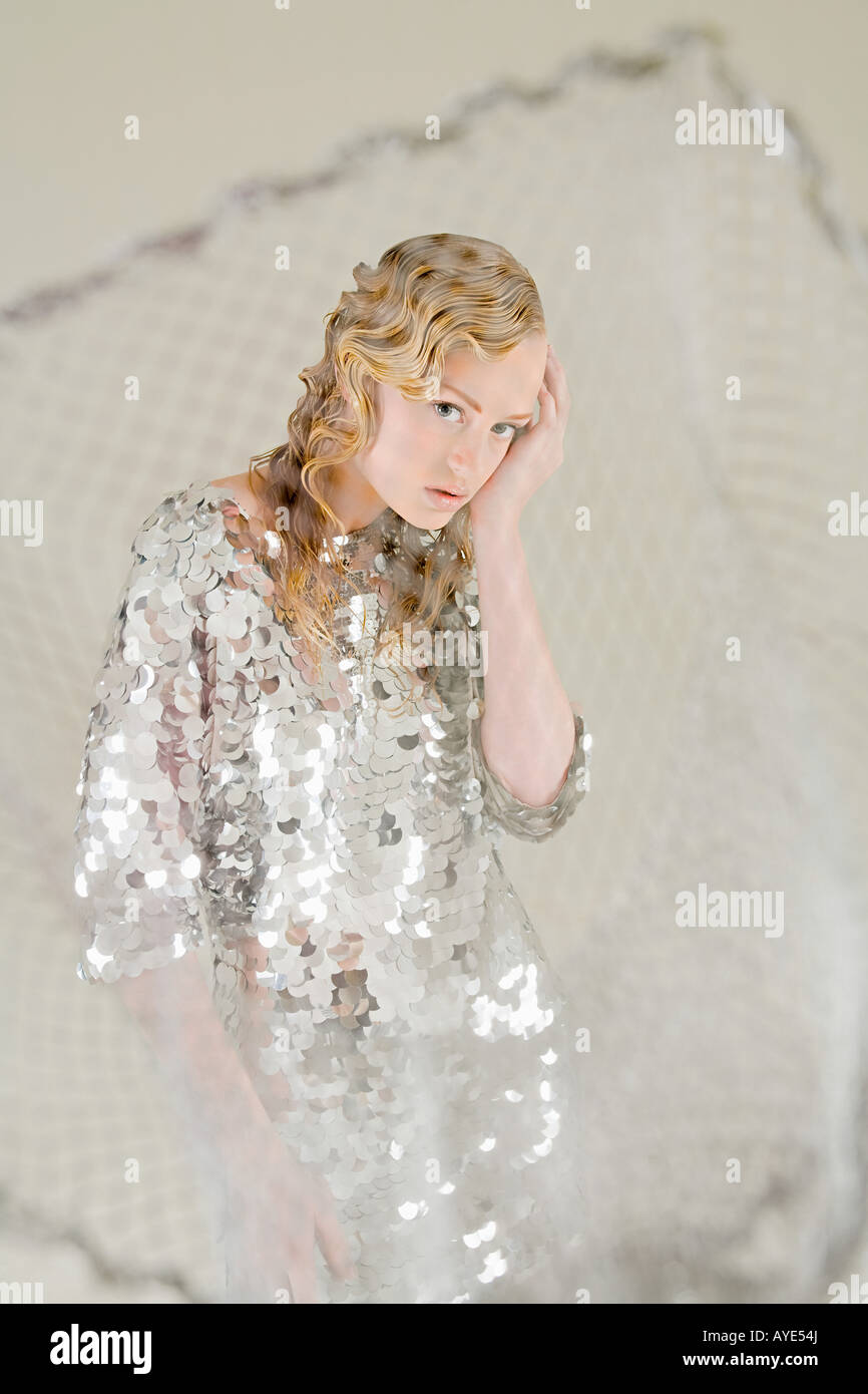 Young woman as fish caught in net - Stock Image