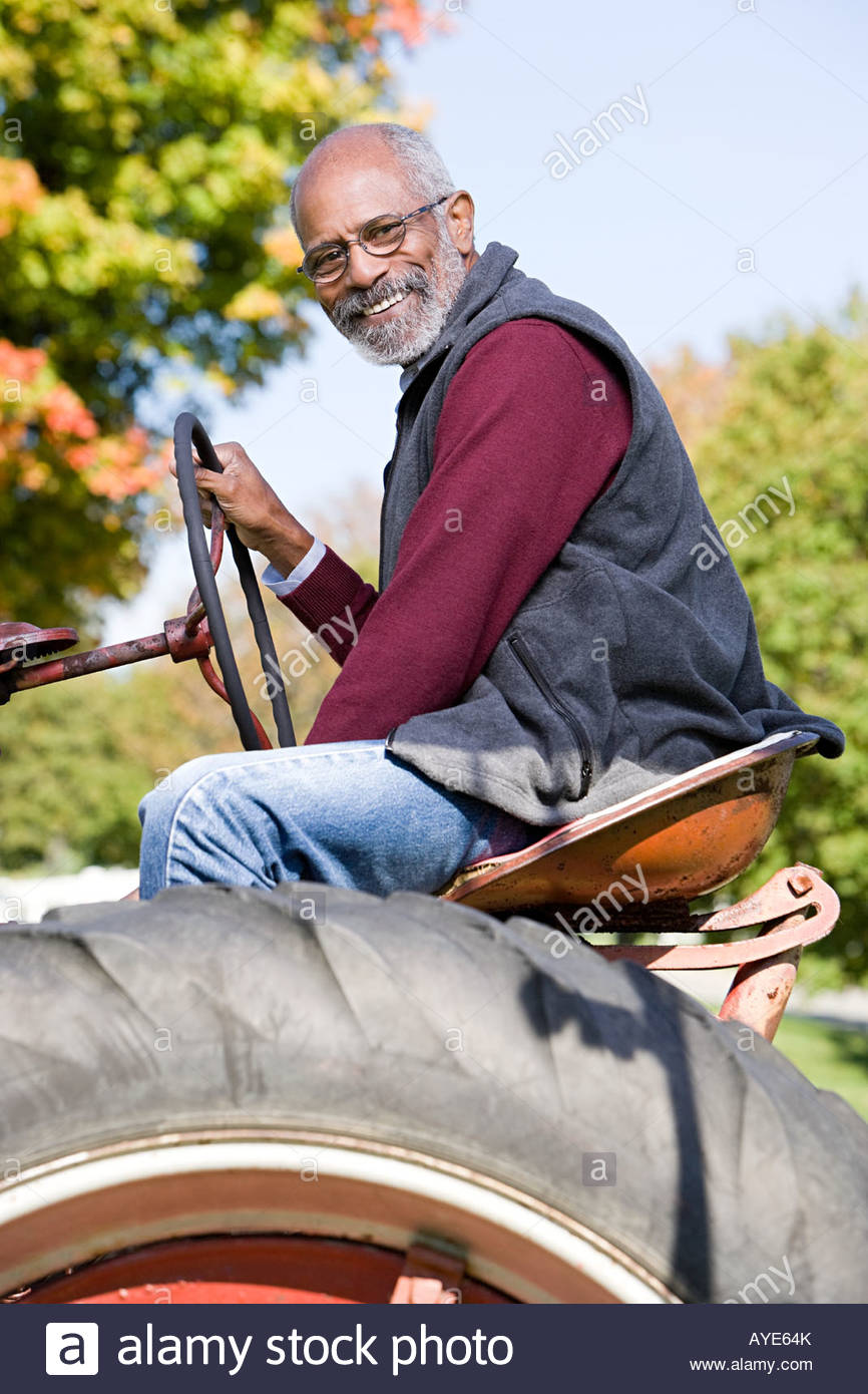 A farmer on a tractor - Stock Image
