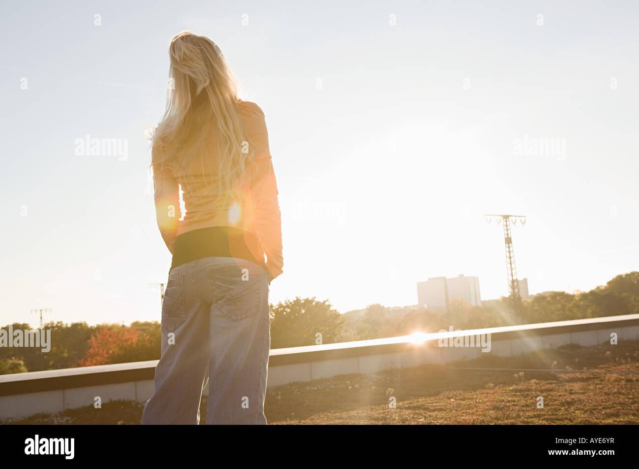 Young woman looking toward the sun - Stock Image
