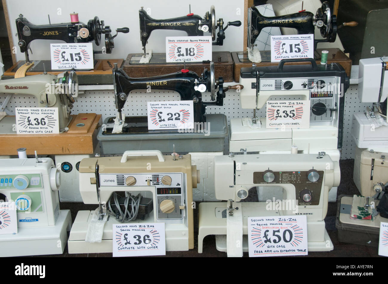 collection of Old manual and electric sewing machines on sale in shop  window - Stock Image