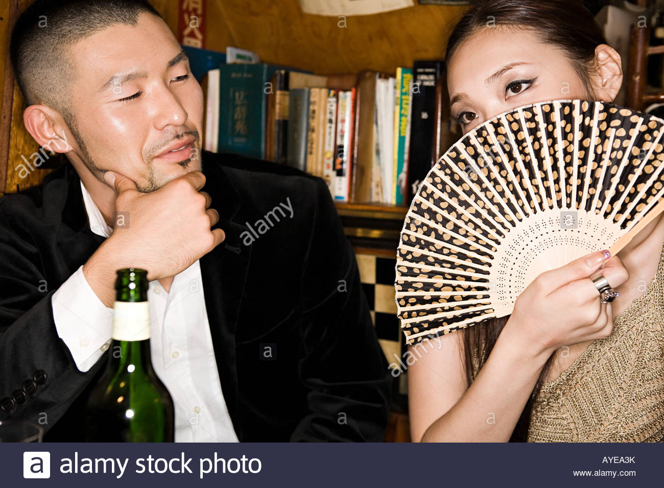 Woman covering her face with a hand fan - Stock Image