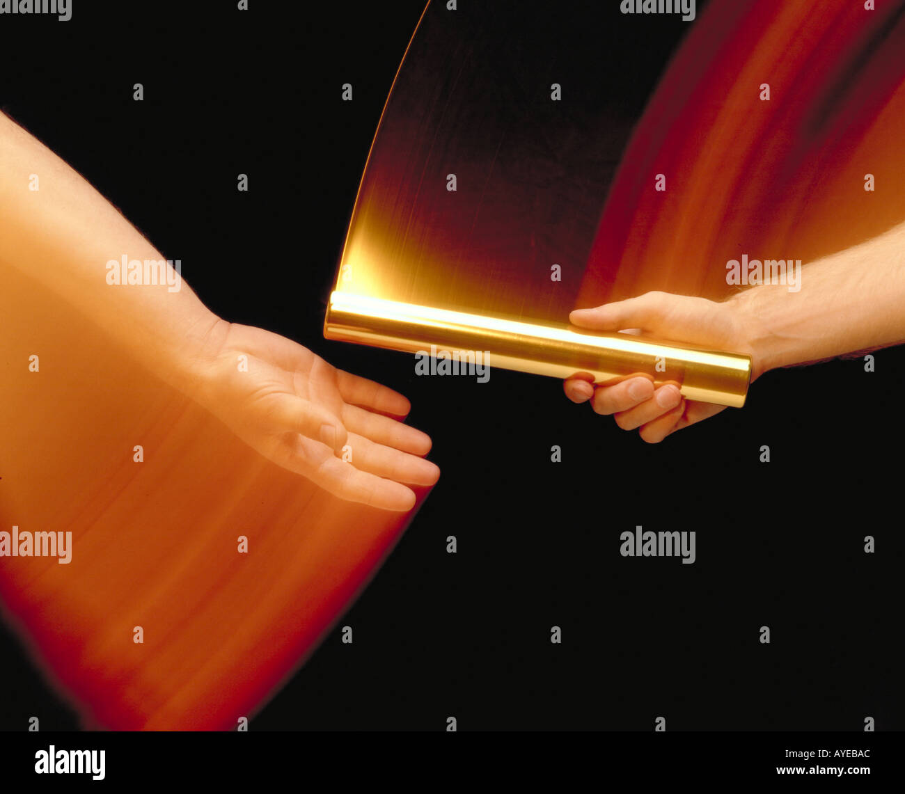 athletes handing off gold baton in motion - Stock Image