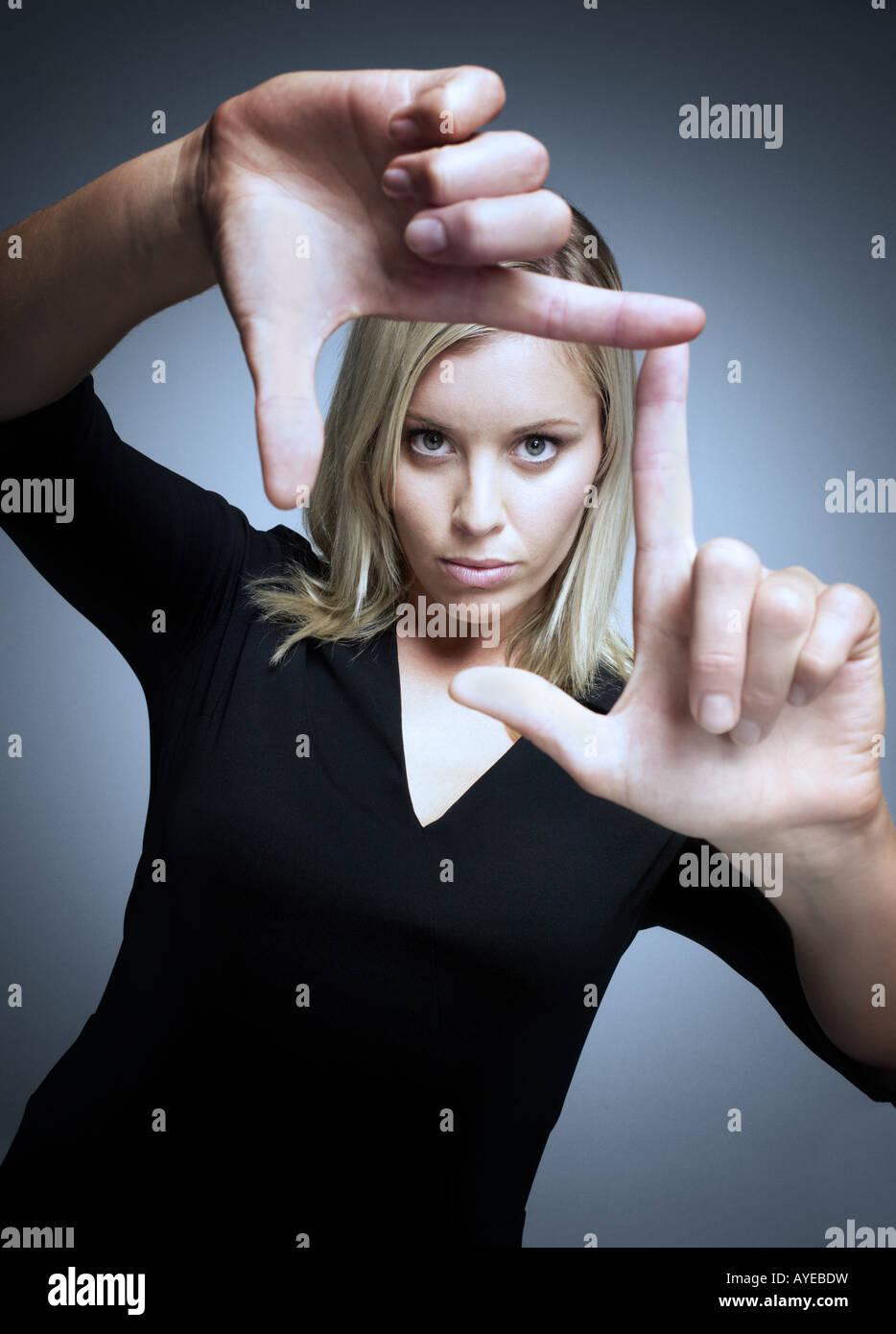 Woman loking through fingers - Stock Image