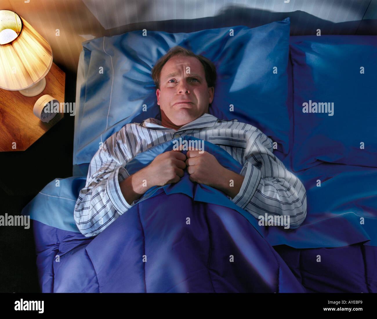 man laying awake in bed not sleeping. - Stock Image