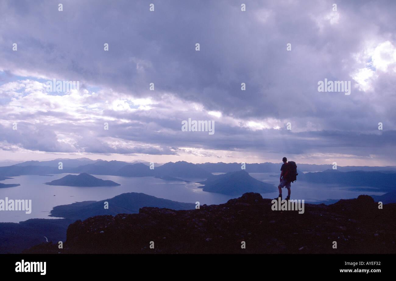Hiker silhouetted above Lake Pedder, Tasmanian Wilderness World Heritage Area, Tasmania, Australia - Stock Image