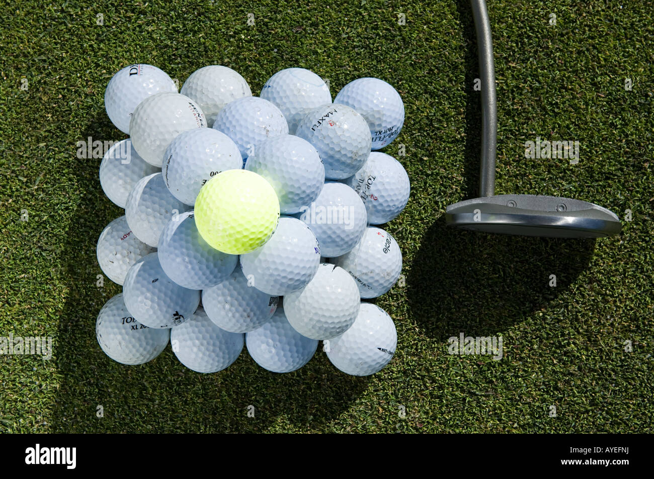 A stack of golf balls and a golf club - Stock Image
