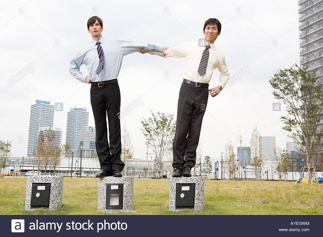 Businessmen holding each others arms - Stock Image
