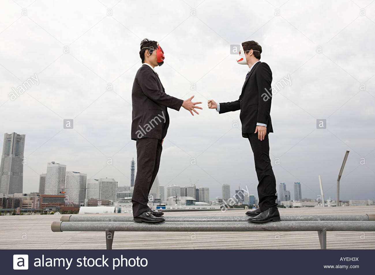 Businessmen wearing masks playing a game - Stock Image