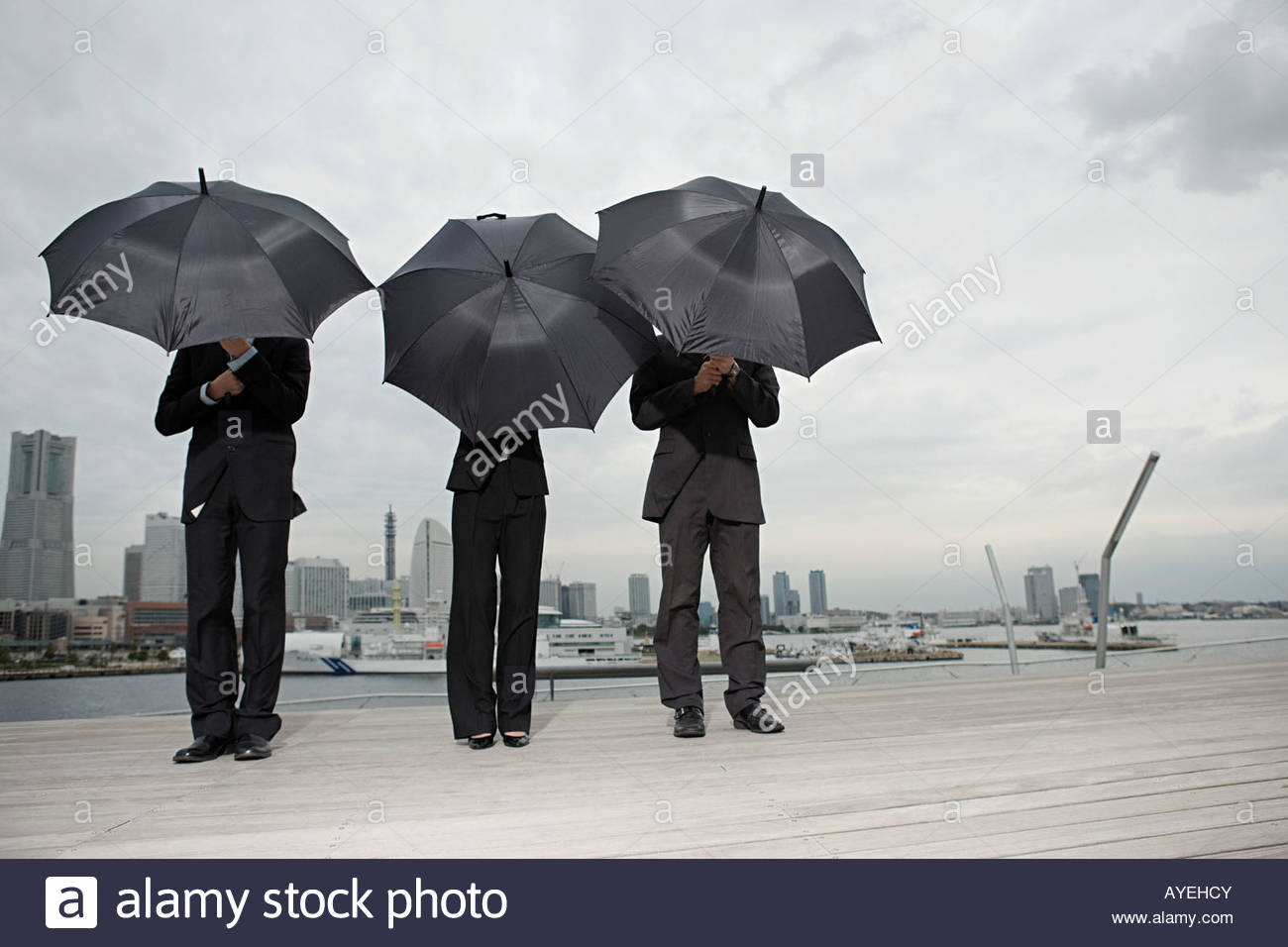 Businesspeople holding umbrellas - Stock Image