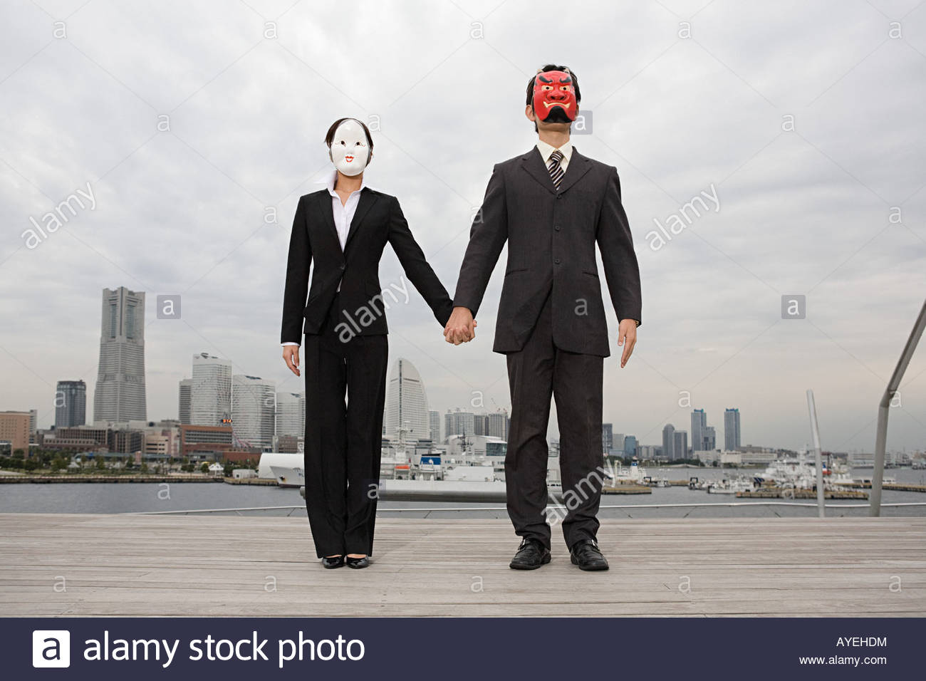 Businesspeople wearing masks holding hands - Stock Image