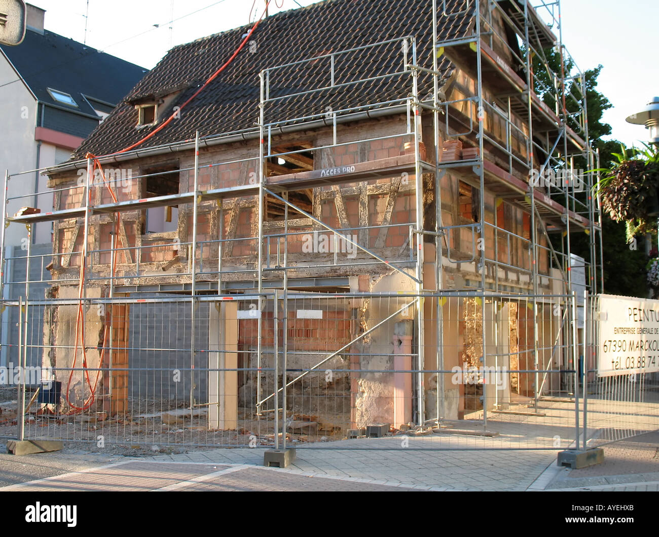 Half-timbered house on renovation, scaffoldings, protection fences, Marckolsheim village, Alsace, France - Stock Image