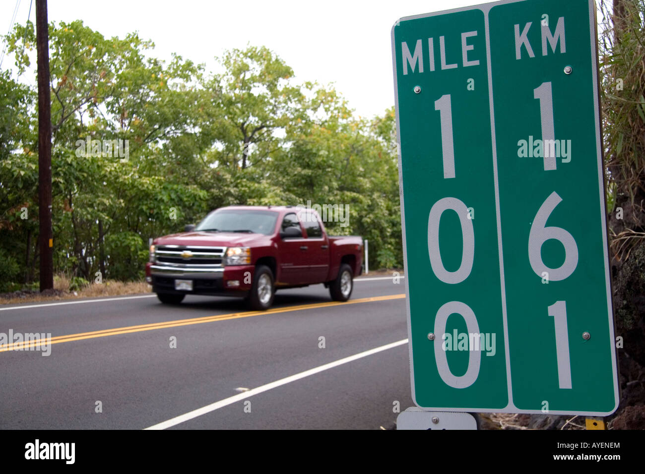 Roadside mile marker showing measurements in miles and kilometers on the Big Island of Hawaii - Stock Image