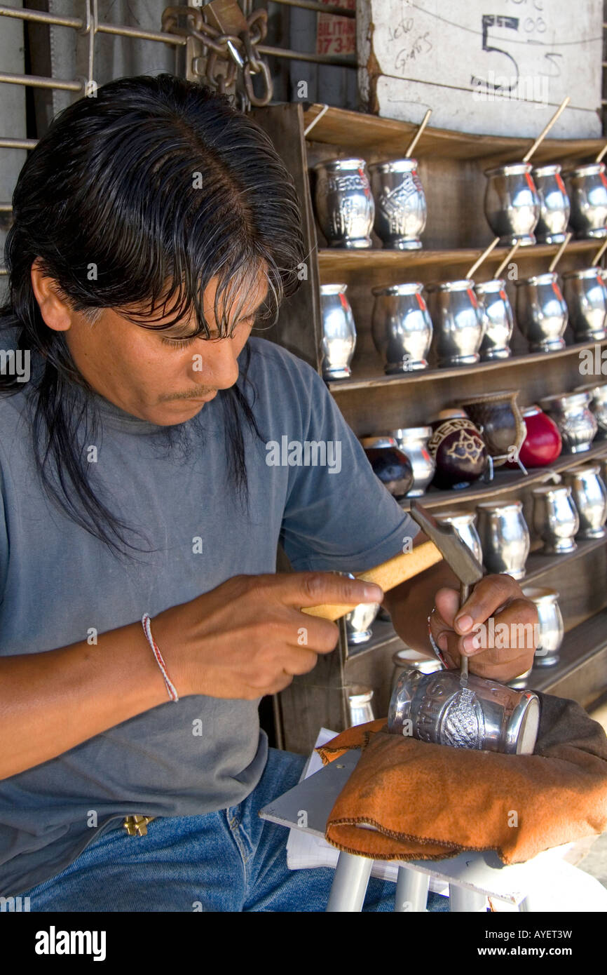 Street vendor engraving on a silver mate cup in Buenos Aires Argentina - Stock Image