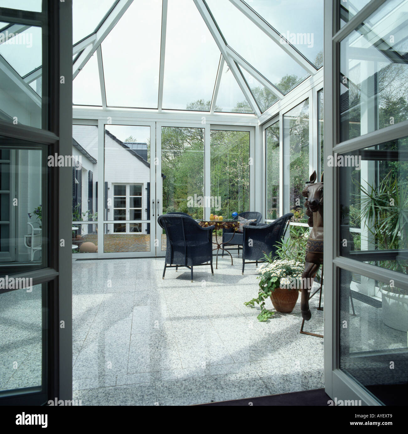 View through open doors to modern glass conservatory with ceramic ...