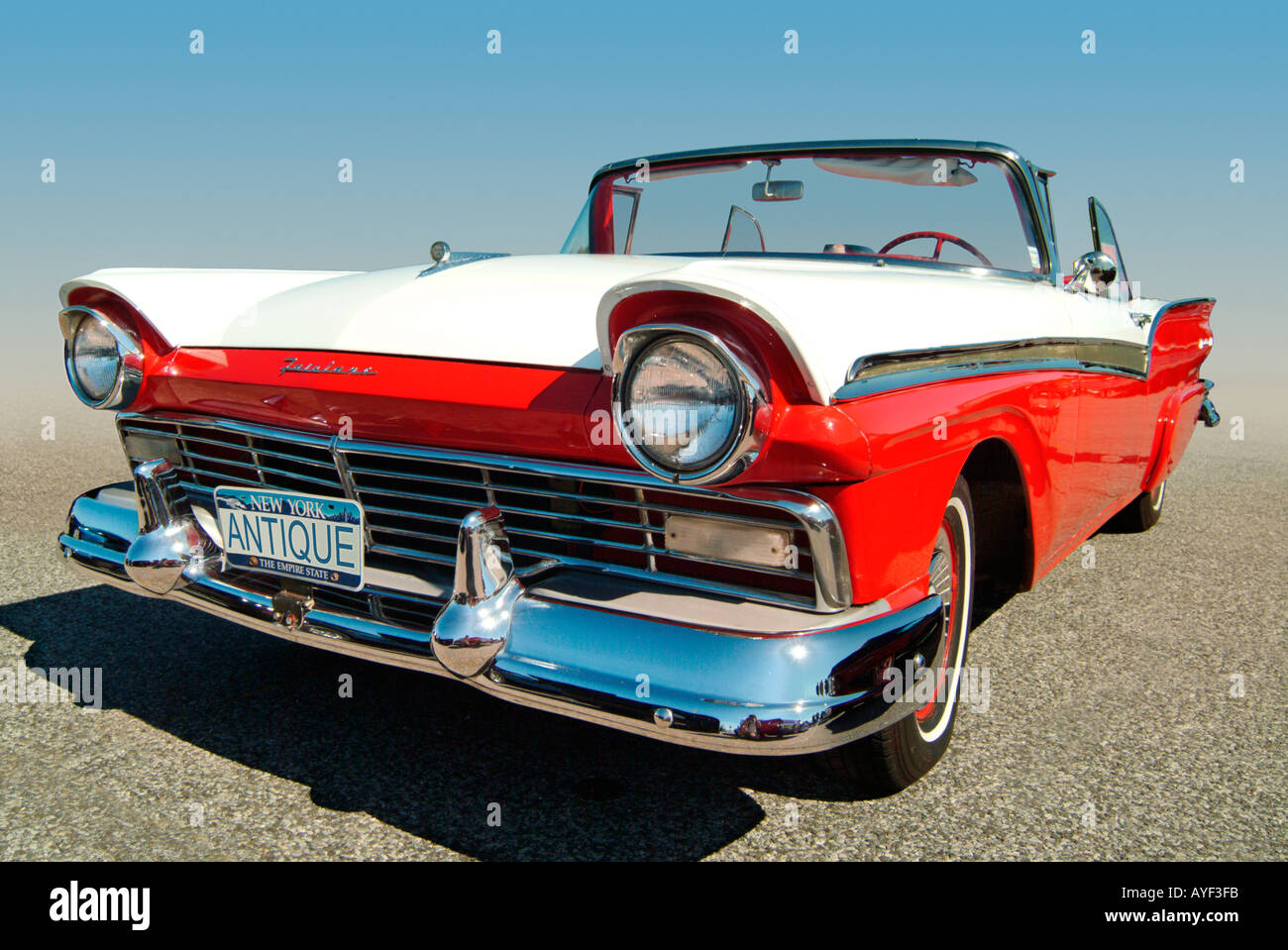 A red and white 57 Ford Fairlane Original license plate number changed to ANTIQUE by the photographer - Stock Image