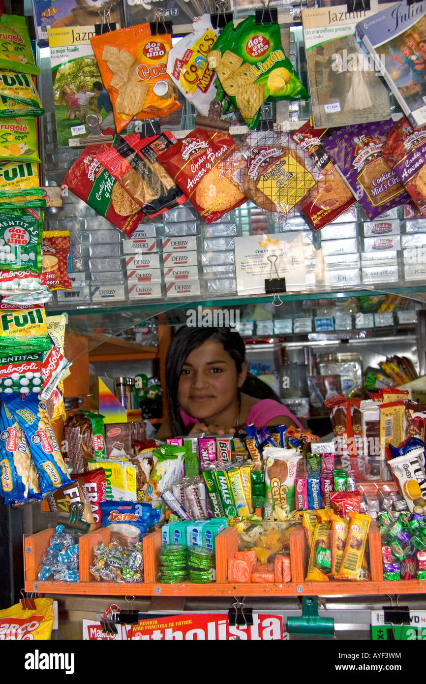 Young girl working in a kiosk selling snacks and magazines in Santiago Chile - Stock Image