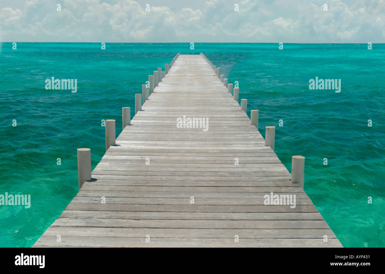 A long wooden pier juts into the Caribbean Sea - Stock Image
