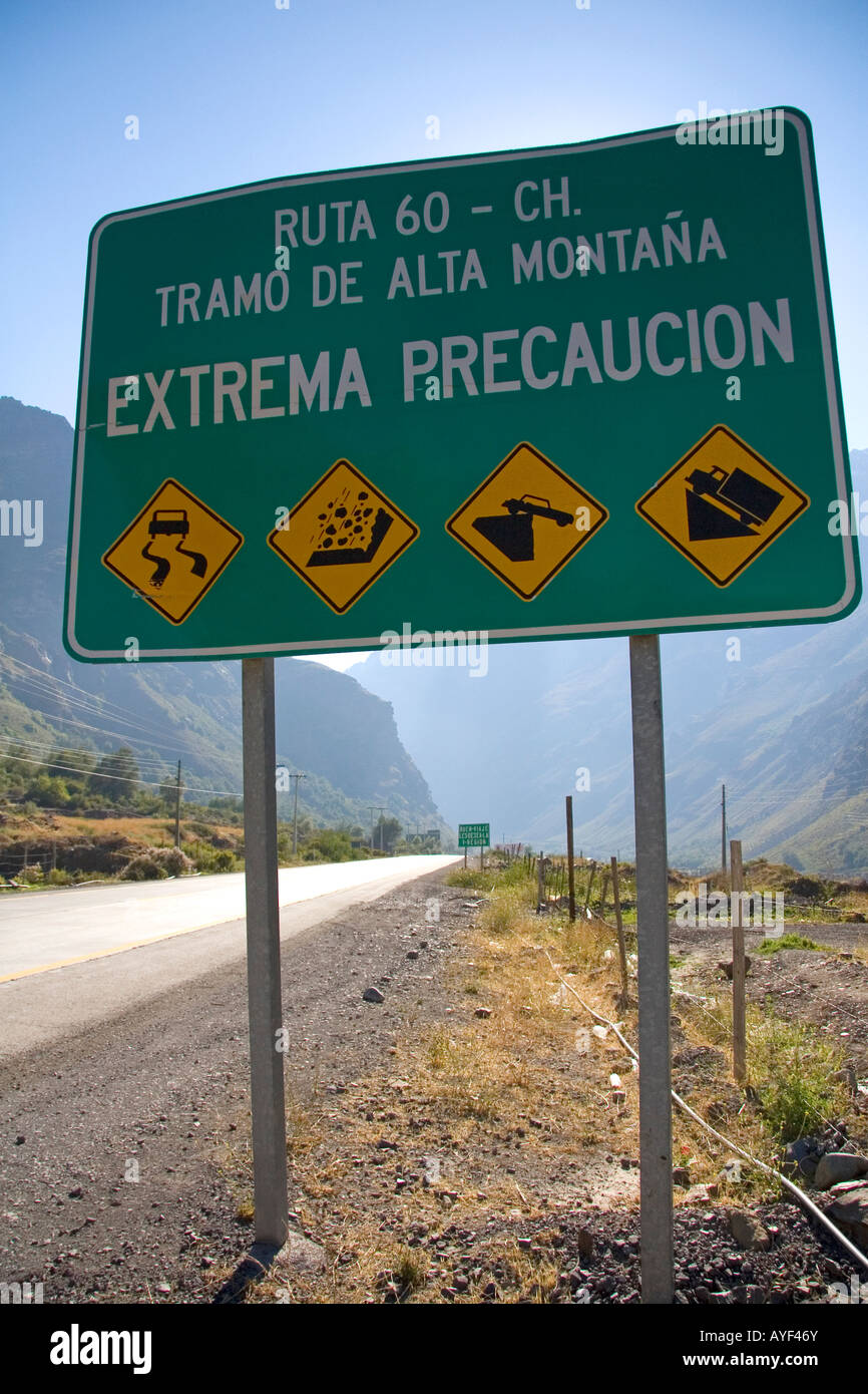 Spanish language road sign warning of hazardous road conditions at the foot of the Andes Mountain Range in Chile - Stock Image