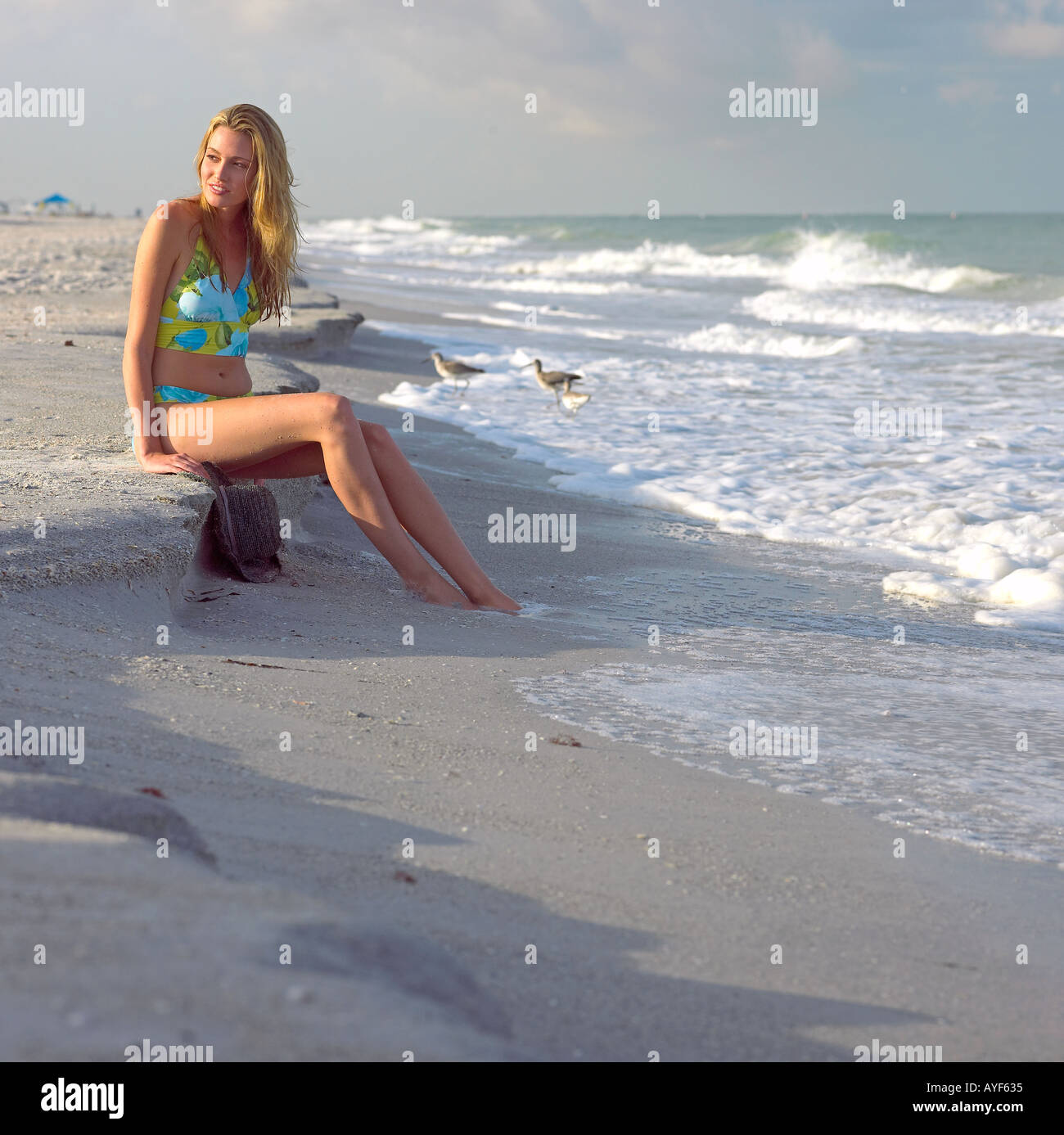 Indian Beach: Young Woman In Swimsuit Sits Peacefully Along Indian Rocks