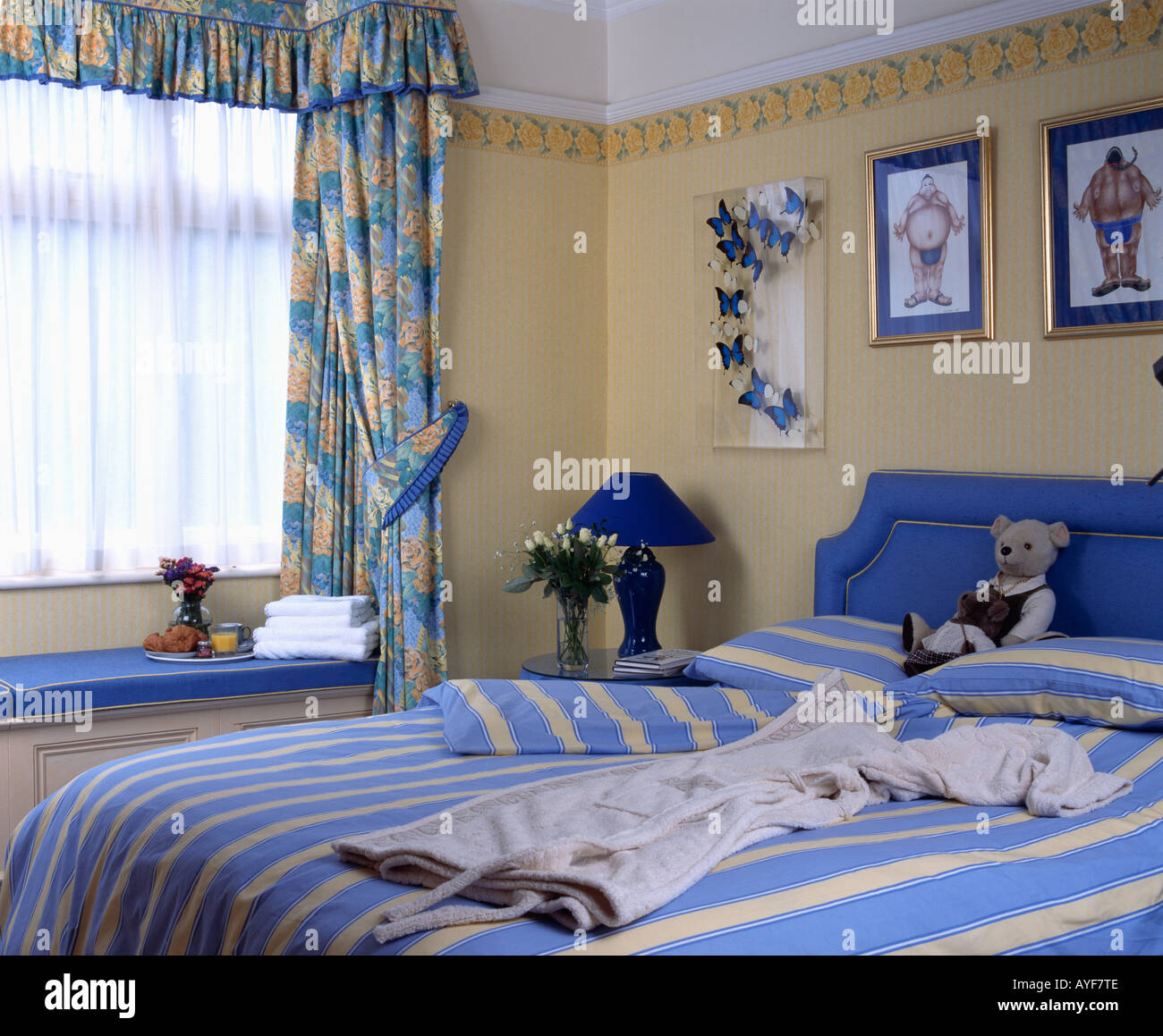 Blue patterned curtains and striped bed linen in yellow bedroom