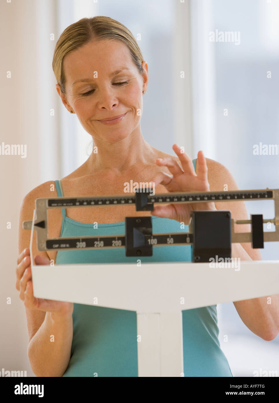Woman weighing self on scale - Stock Image