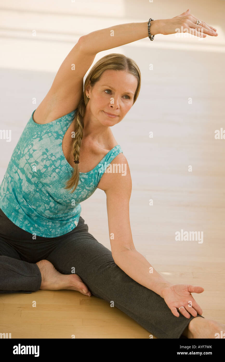 Woman stretching on floor - Stock Image