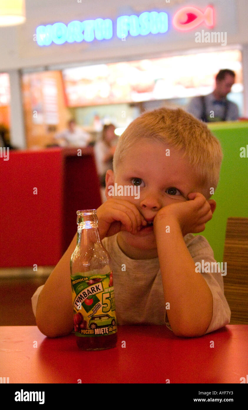 Thoughtful boy eating in a fast food restaurant at Manufaktura entertainment center. Lodz Central Poland - Stock Image
