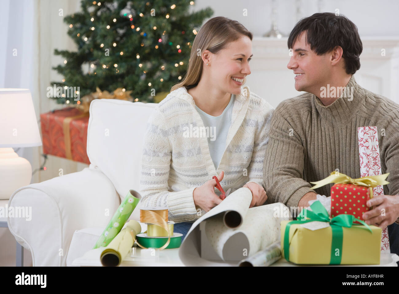 Couple wrapping Christmas gifts - Stock Image