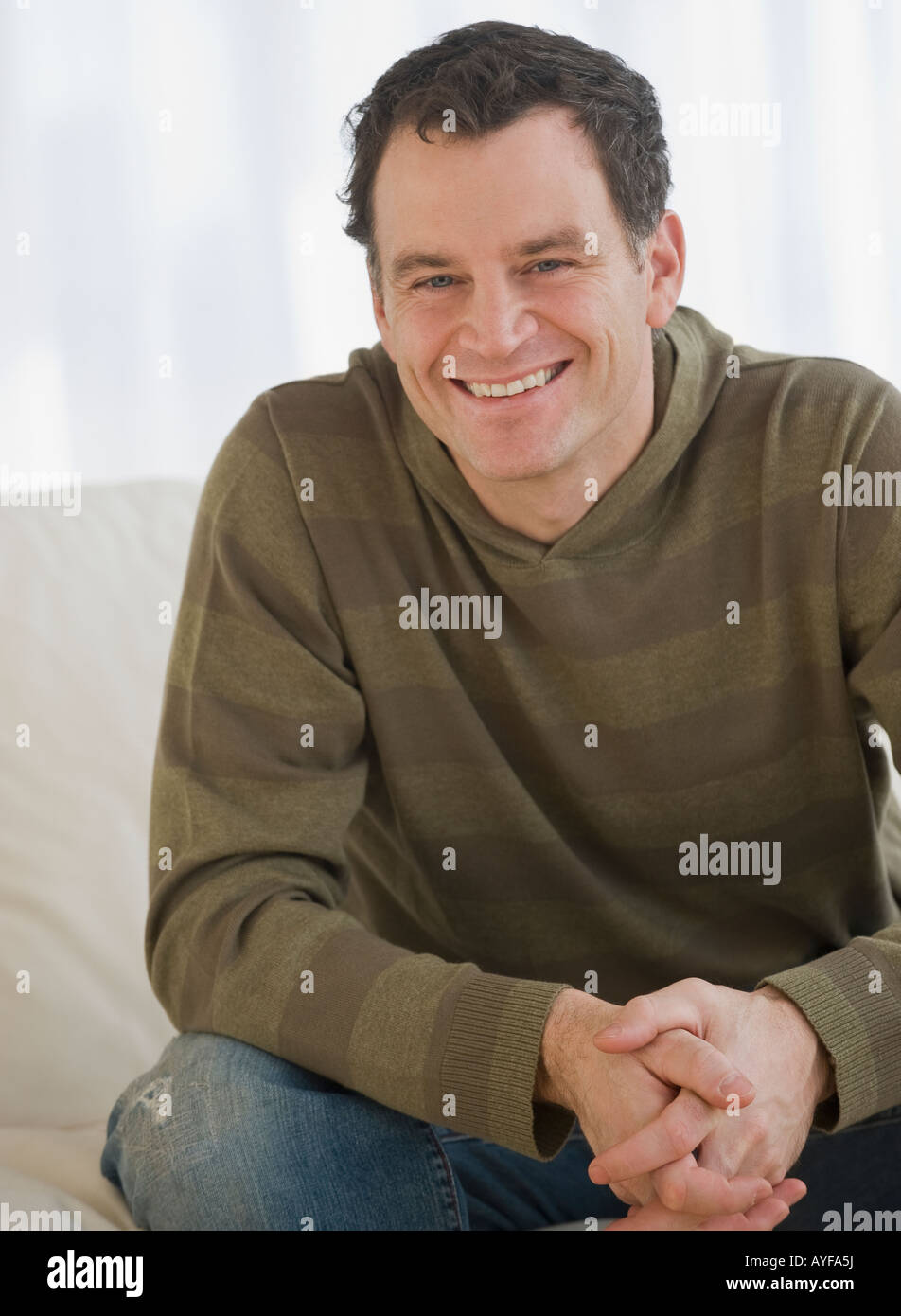 Man sitting with hands clasped - Stock Image