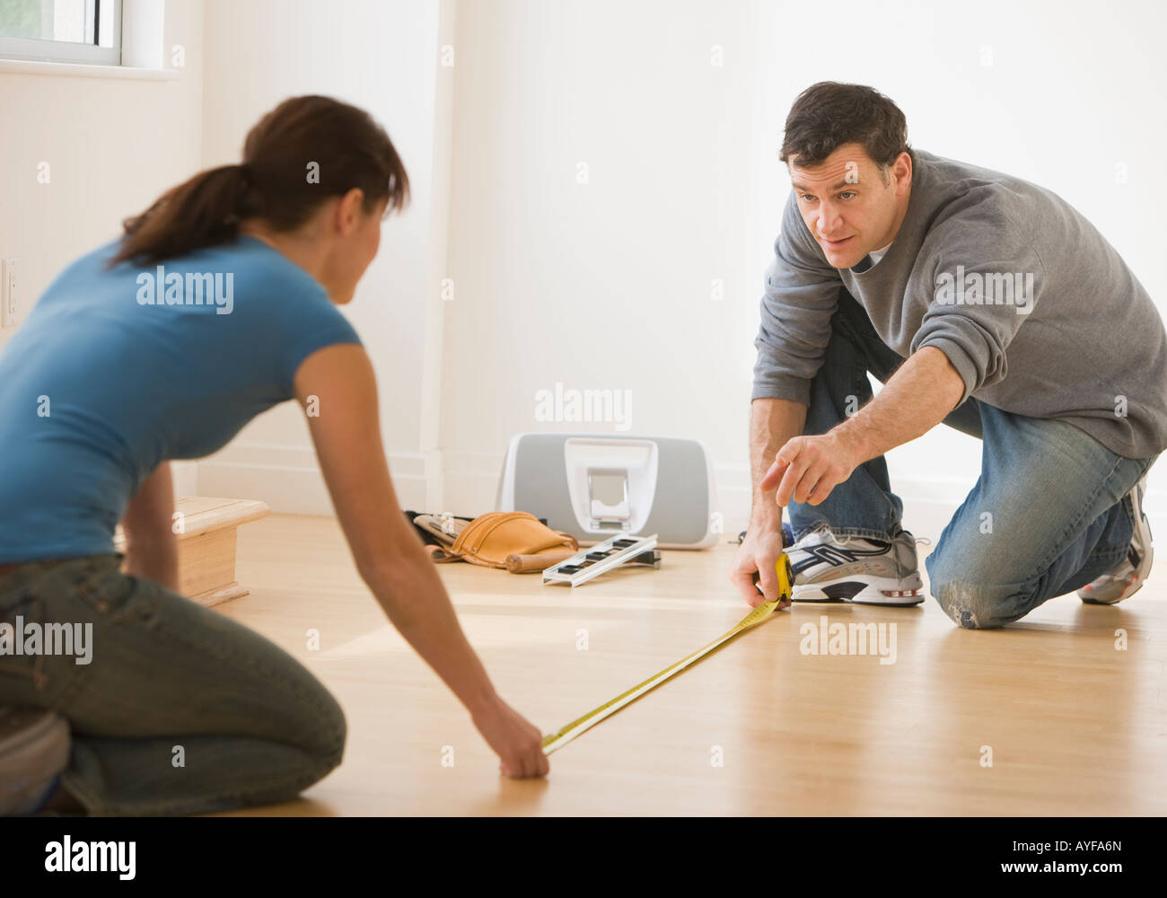 Couple measuring floor with tape measure - Stock Image