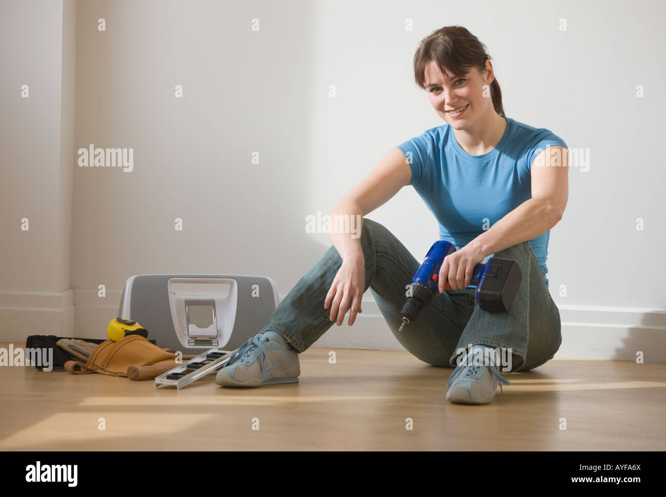 Woman sitting on floor holding cordless drill - Stock Image