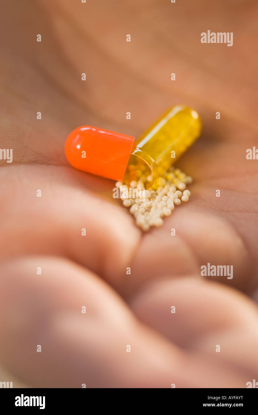 Close up of open medication capsule in man's hand - Stock Image