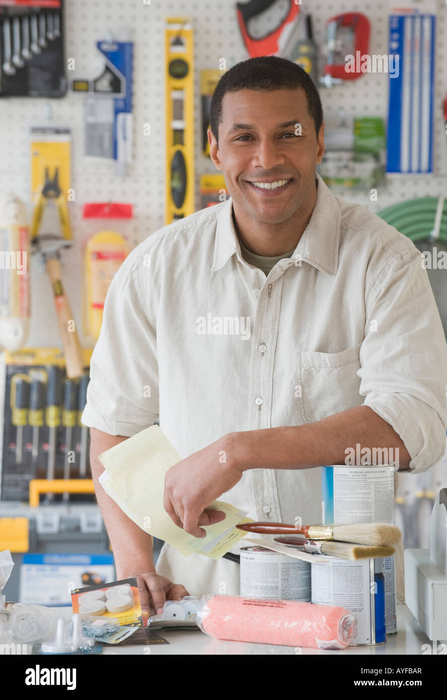 African sales clerk, counter at hardware store - Stock Image