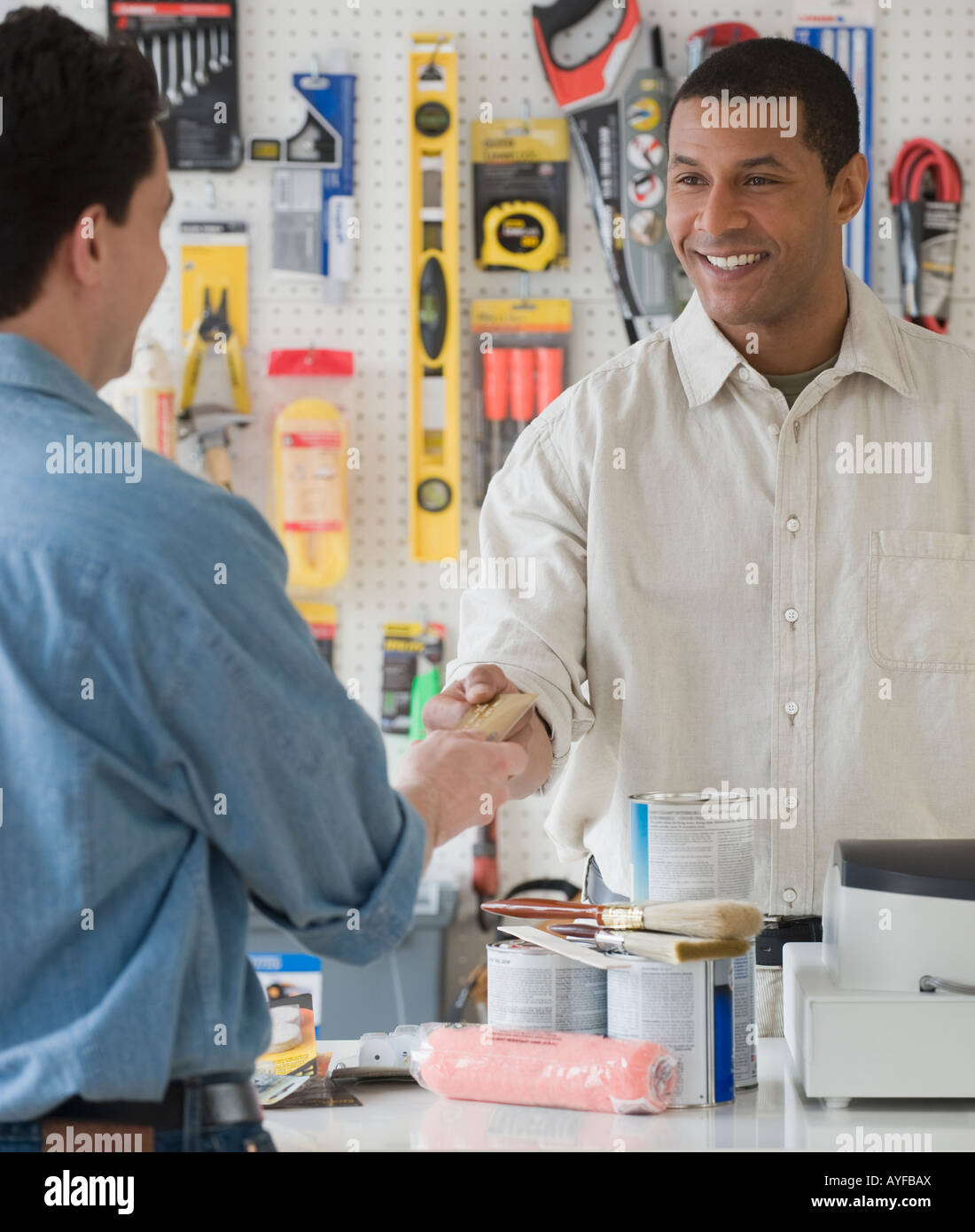 African sales clerk at hardware store handing over credit card - Stock Image