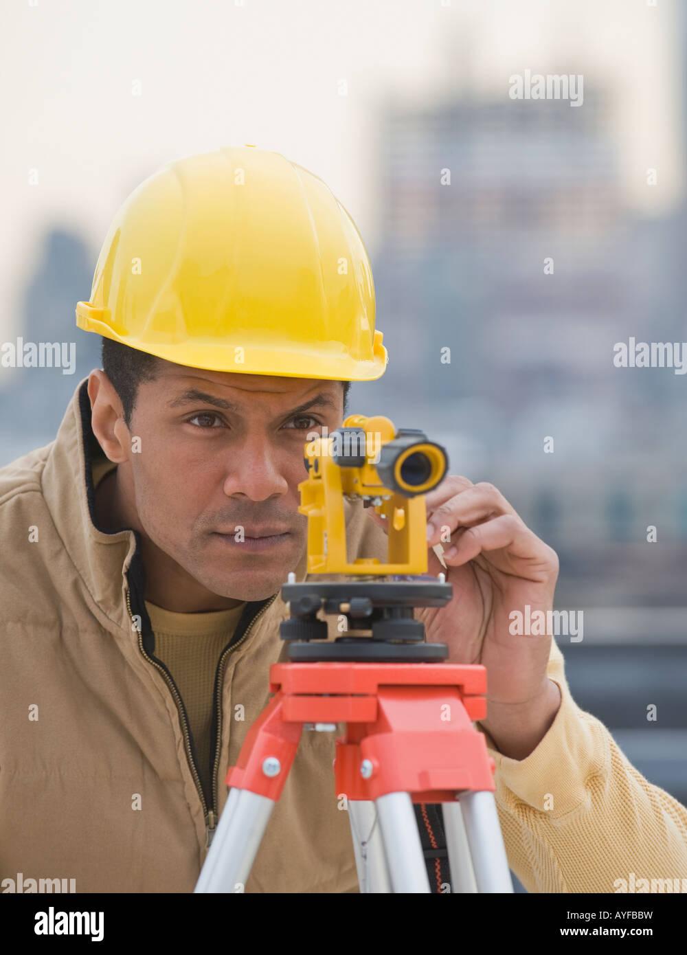 African male surveyor looking through measuring device - Stock Image