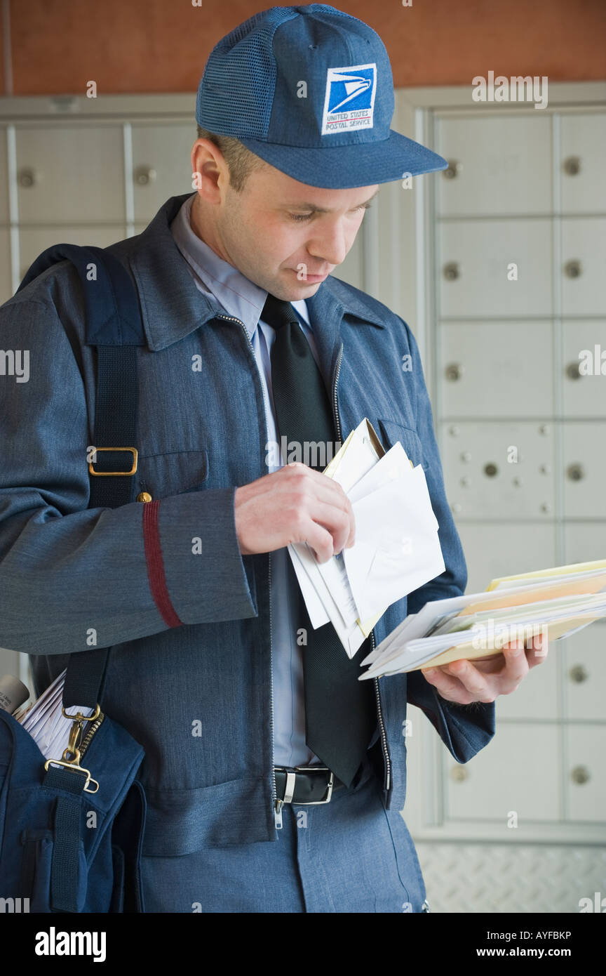Male Postal Worker Looking At Mail Stock Photo Alamy
