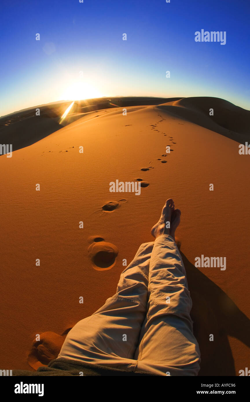 Tourism Legs of person relaxing and watching sunset in the sand dunes of Erg Chebbi area Sahara desert Morocco Model released - Stock Image