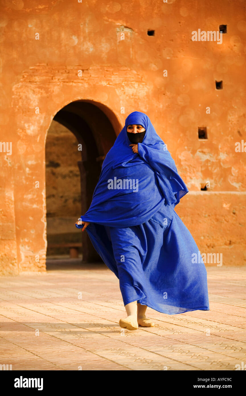 Muslim women wearing the traditional chador walk past the ramparts that surround the medina Morocco - Stock Image