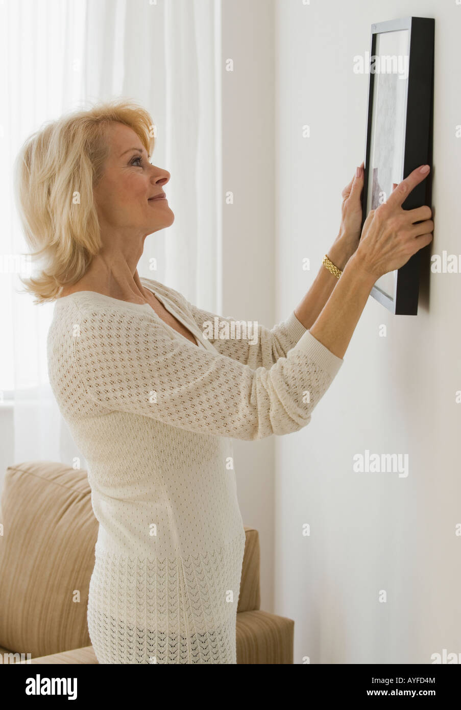 Senior woman hanging picture on wall - Stock Image