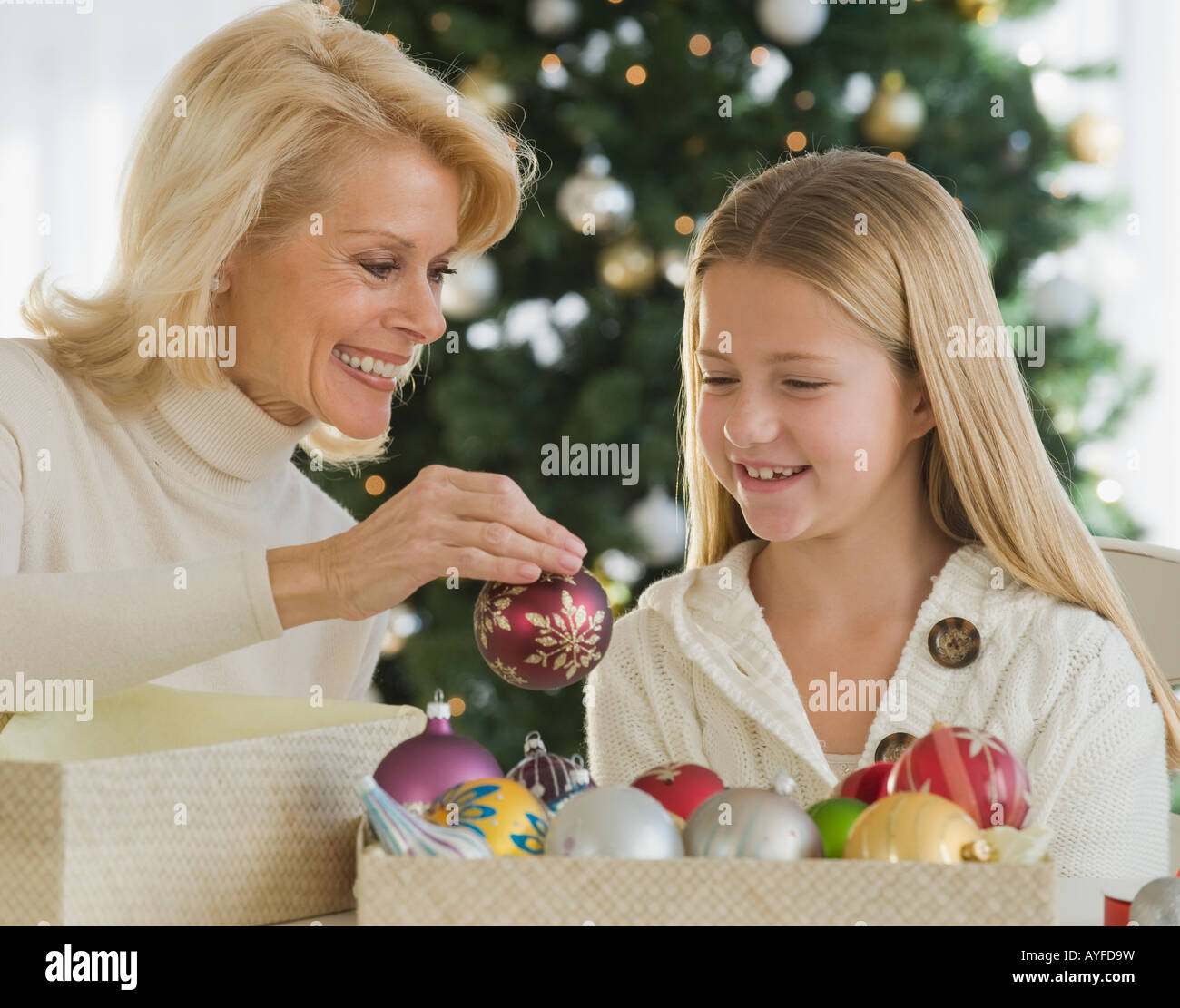 Grandmother and granddaughter looking at Christmas ornaments - Stock Image