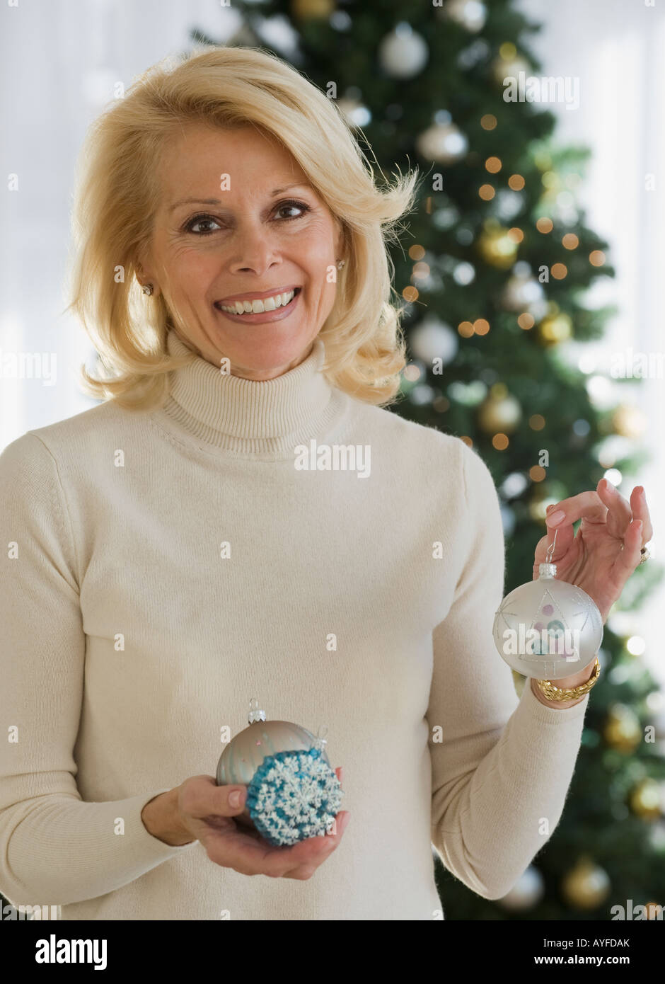 Senior woman holding Christmas ornaments - Stock Image
