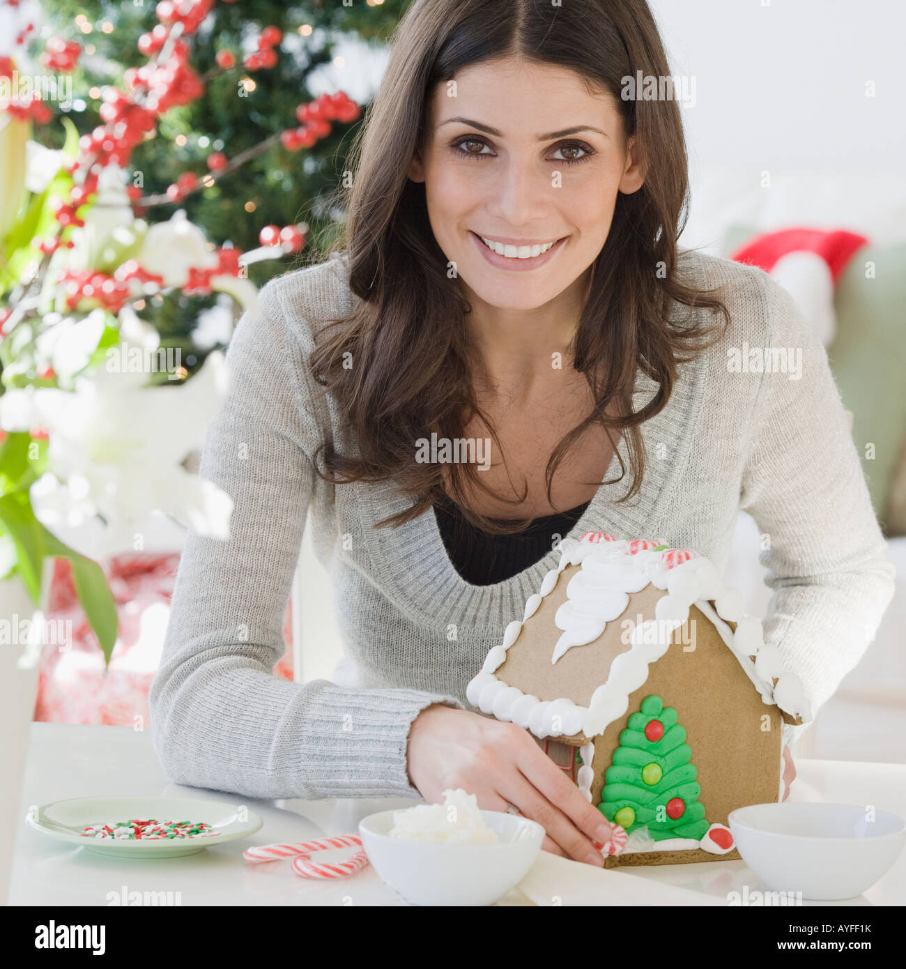 Woman making gingerbread house - Stock Image