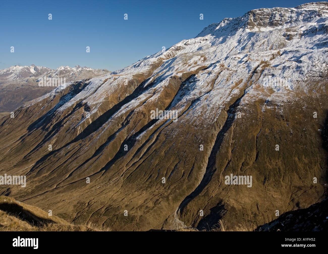 Erosion on mountains just east of the Furka Pass south Switzerland After first autumn snow - Stock Image