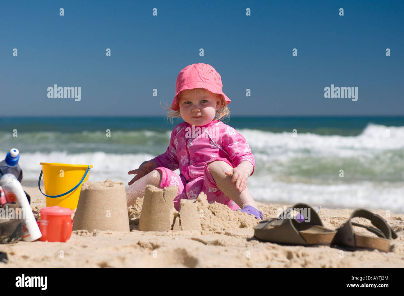 Toddler playing on the beach in Ilha de Tavira, Portugal - Stock Image