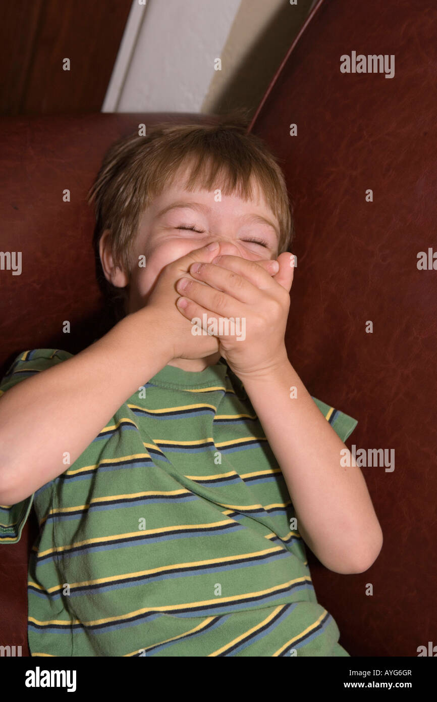 five year old boy covering mouth with both hands, trying not to laugh Stock Photo